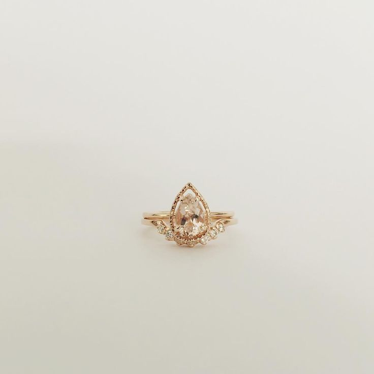 Handmade custom pear cut morganite with faceted halo, with matching arc diamond band.