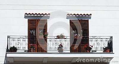 Balcony with two beautiful wooden doors and flower pots