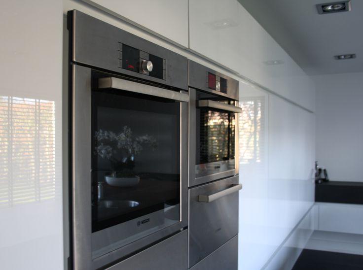Op maat gemaakte kastenwand met inbouwapparatuur in de keuken ...