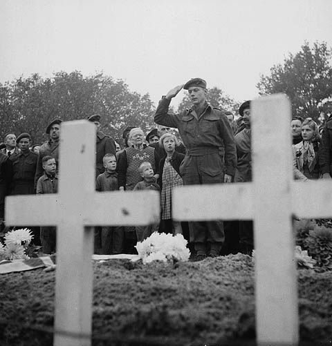 Major William Ewing saluting at the funeral of 55 members of 'A' Company, The Black Watch ( Royal Highland Regiment) of Canada. Ossendrecht, Netherlands 26 Oct 1944.