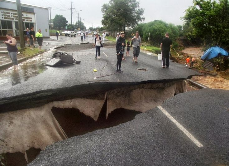 Local residents inspect a road that collapsed when a flash flood swept through Toowoomba, Australia.