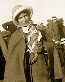 A nurse dressed in uniform cape, hat and gloves, holds a kitten