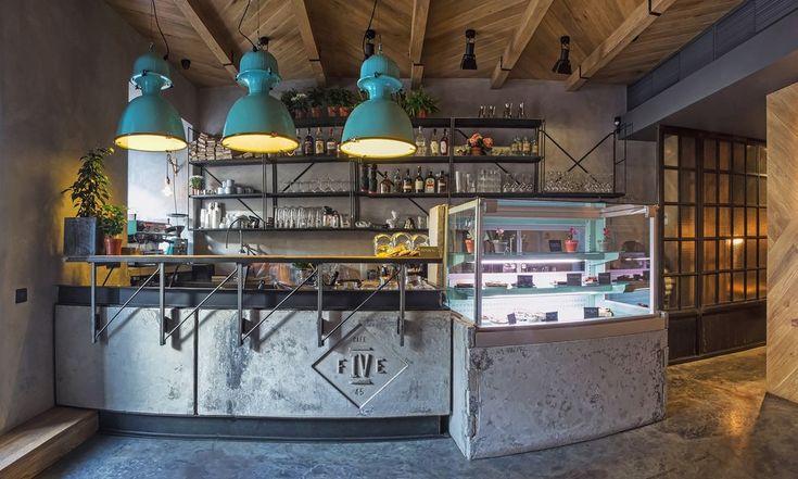 Миксовый код города легко читается в интерьере кафе: он функционален, при минимуме декора «работают» плоскости стен, пола и потолка. Бетон контрастирует с дубом, оттеняя изделия из металла. Технические светильники, выкрашенные в фирменный бирюзовый цвет заведения, перекликаются со стульями на террасе и кофемашиной La Marzocco в окне.