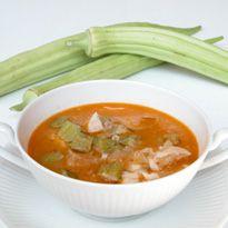 Cómo hacer Sopa de quimbombó. Primero cortamos los quimbombós en rodajas, descartando las cabezas. También picamos la cebolla, machacamos el ajo, y troceamos el tomate, dejándolo sin piel ni