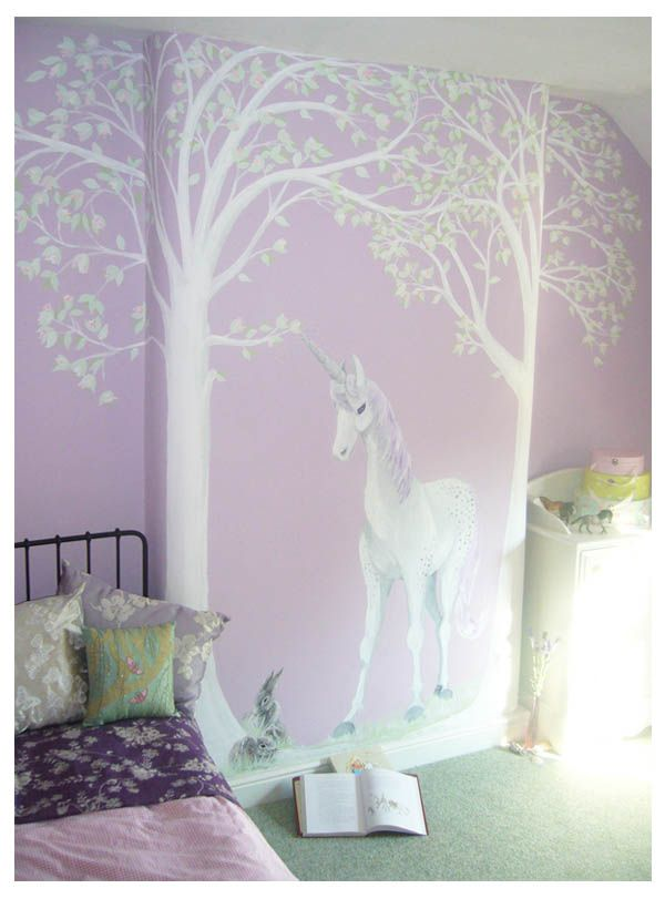 Mural designed to order and hand painted Unicorn, underneath blossom trees. The trees are painted around the curve of the chimney breast. The horn is silver with silver magic sparkles around the tip. The child's pet rabbits have been included at the foot of the tree.