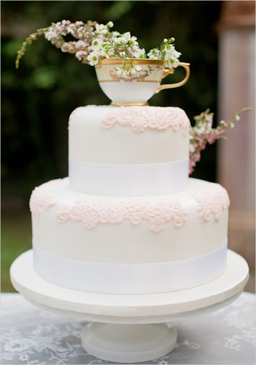 Cake love: a traditional white wedding cake with a dainty teacup topper   The Natural Wedding Company