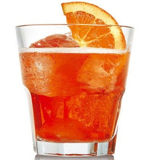 """The Aperol Spritz is of Italian origins and is a refreshing combination of Aperol, Prosecco and a splash of club soda, garnished with an orange slice. Its orogins date back to WWII when the Austrian/German soldiers used to reduce the alcohol content of wine with a """"spritzen"""" (to spray) of soda water. The drink originated in the Venice region and spread in all north east of Italy, and only in recent years reached national and international fame."""