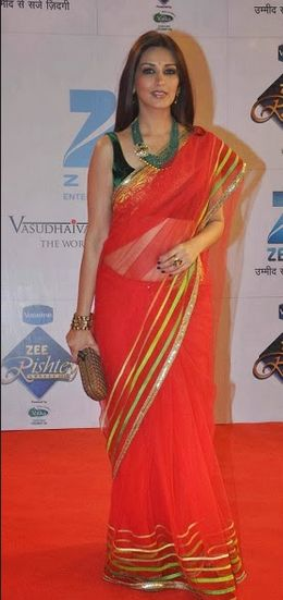 Sonali Bendre in beautiful red designer net saree at Zee Rishtey Awards 2013. Designed by Manish Malhotra. It is a net saree with gold embellished border,followed by multicolor stripes. Paired with green designer sleeveless saree blouse.