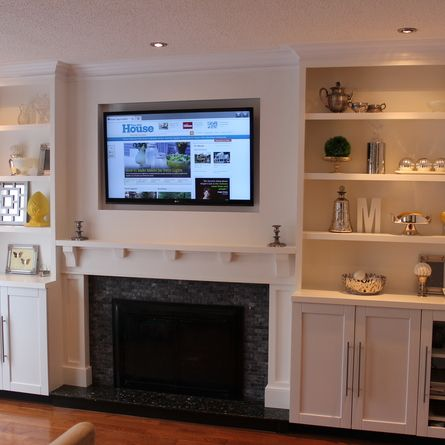 Stock cabinets outfitted with custom shelving, trim and a new mantel provide an attractive anchor and useful living room storage and display. | thisoldhouse.com/yourTOH