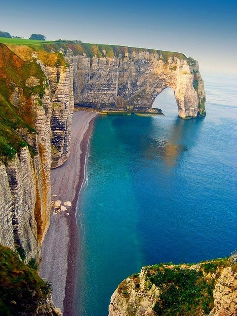 Sea Cliffs in the north west of France in Normandy. Along its northern coastline is the small town of Etretat, globally famous for its beaches and chalky white cliffs carved by nature. Three massive natural stone arches (Porte d'Aval, Porte Amont, Manneport) at both ends of Etretat Plage inspired painters Boudin, Monet and Manet.