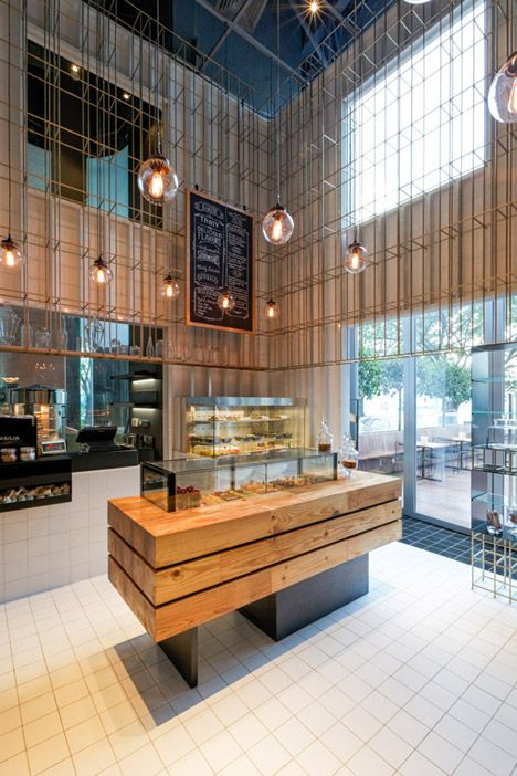 A cage-like grid of brass poles surrounds the upper section of this double-height patisserie in Shenzhen, China.