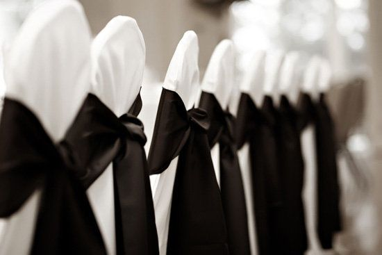 White chair covers with black satin sash