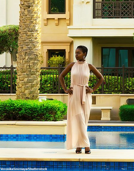 Woman poses in front of swimming pool and palm tree in a long beige maxi dress.