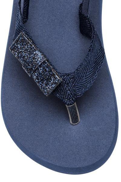 Slippers met een rubberen teenriem (in mt 24/25 en 26/27 met een elastiekbandje rond de hiel). De slippers hebben een decoratieve stoffen bloem vooraan en e