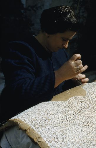A woman sews an intricate piece of lace. Pag Island, Croatia,