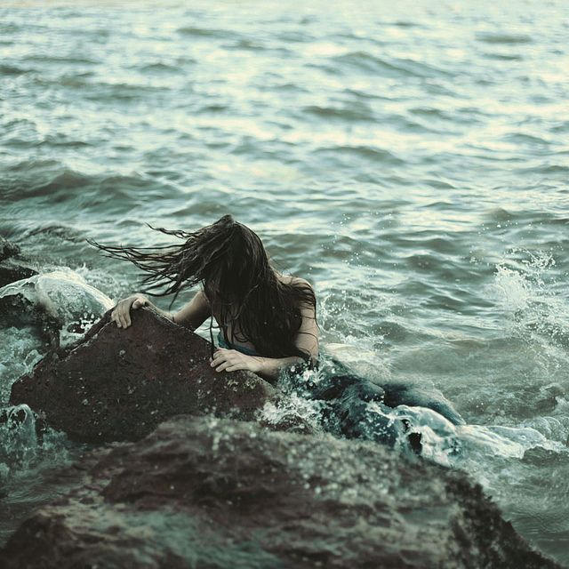 She held onto the rock, the waves splashed against her. Tears streamed down her cheeks, mingling with the salt water. Her heart was breaking...