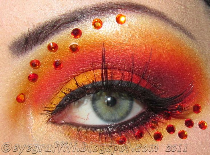 Fiery shades of orange eye shadow accented with orange jewels.
