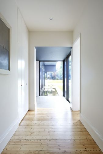 Hardwood floors line this hallway, contrasting with the white walls and ceiling