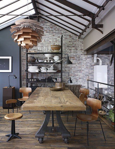 industrial dining room with thick wood top of this dining table is supported by a cast-iron factory table base