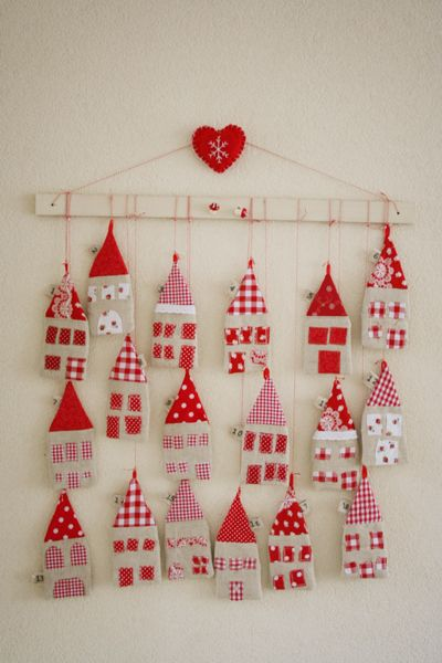 advent calendar - fabric houses with envelope closures in back hung from string off strip of wood