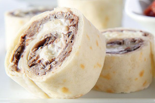 Tortillas are rolled up with puréed black beans, cream cheese, pepperjack cheese and sour cream inside, then cut crosswise into festive appetizers.