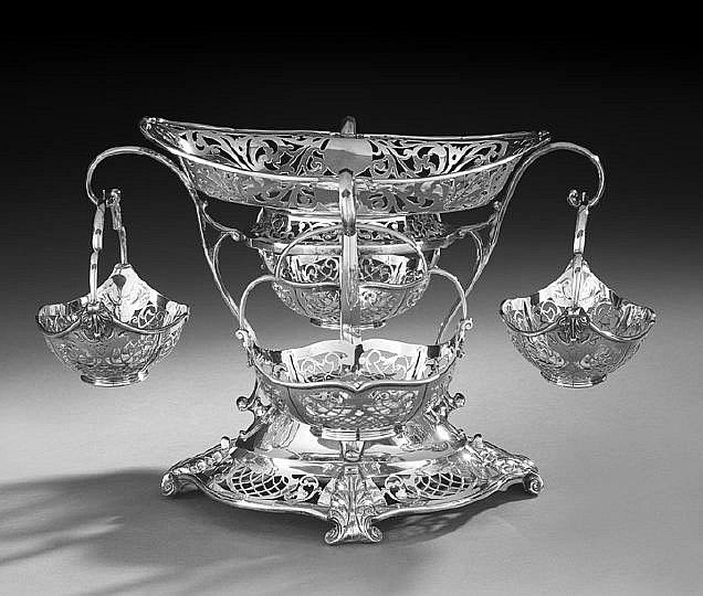 George V Sterling Silver Epergne, hallmarked Sheffield, 1912-1913, by Martin, Hall & Co., comprising an oval pierced cavetto frame raised by four scrolling arms above a domed serpentine-lobed base with pierced lattice banding and four acanthus scroll feet, the arms each with a dangling basket with lobed strap handle and reticulated en suite, the central frame fitted with an associated pierced basket
