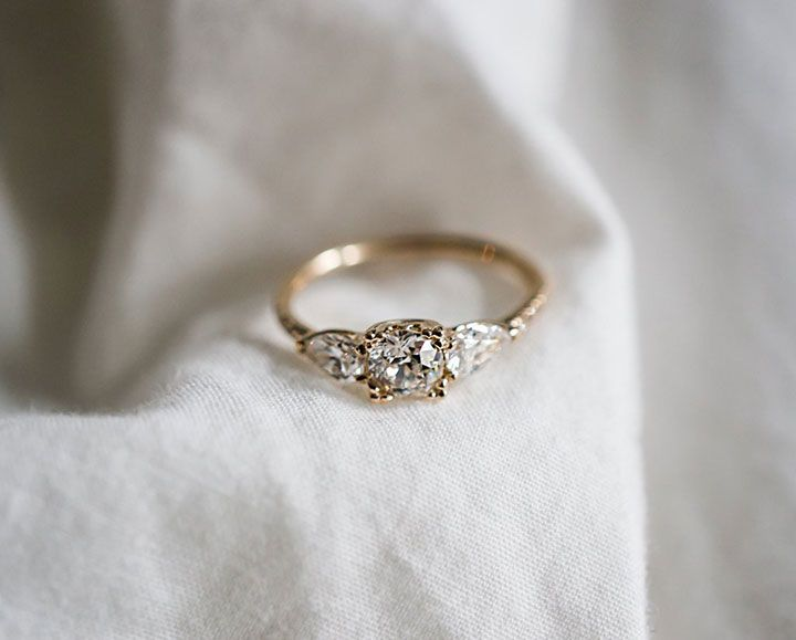 Bespoke diamond engagement ring with reclaimed pear shape side diamonds in recycled yellow gold.