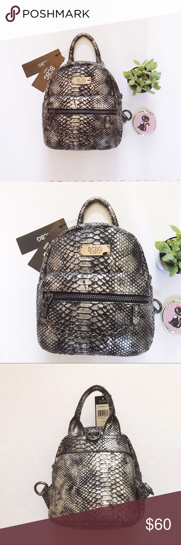 """✨NWT✨ BCBG Paris Main St Petite Backpack in Silver Chic and trendy, this little backpack is perfect for any occasion. Features a short handle to carry with your hand or to keep it hands-free, hook the straps to carry it as a backpack. Front features a zip pocket with chain, inside has an open pocket (for cell phone). Measurements are approximately 8 x 8"""". New with tags, MSRP $125. BCBG Bags Backpacks"""