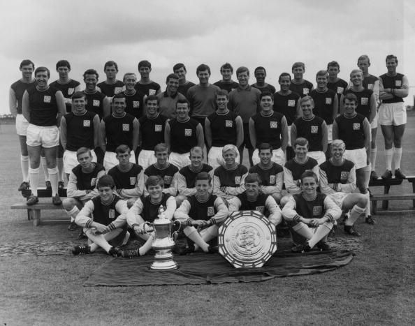 What a great year to be born and smack bang in  undoubtedly West Ham's golden era. Caption:18th August 1964: West Ham United with the FA Cup and Charity Shield trophies. The youth team are in the first two rows. The English World Cup winners Geoff Hurst (third row, fourth from right) and Bobby Moore (second row, first right) are also present. (Photo by William Vanderson/Fox Photos/Getty Images)
