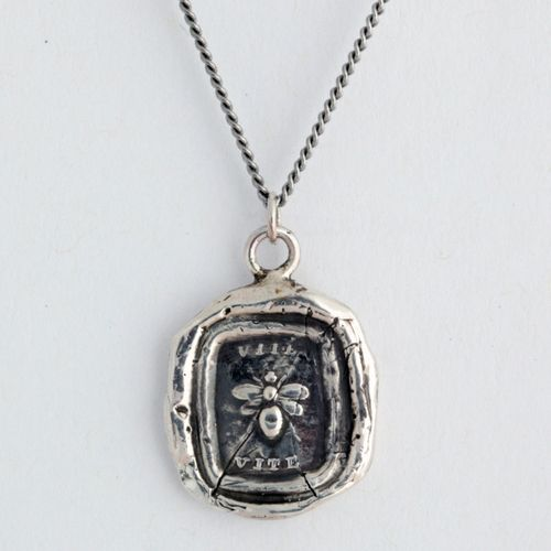 This handcrafted talisman necklace features a bee: a symbol of life and creativity. Written above and below the bee is the word Vite, which is the Latin word for life.