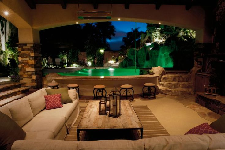 The use of lighting from all directions accentuate the tropical feel of this outdoor space. Lights within the pool, landscape lighting illuminating the waterfall and foliage, and recessed lights set low in the cabana provides a serene view of the lagoon-like pool area.