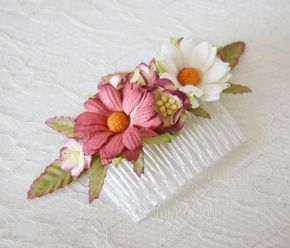 A gorgeous flower comb with large aster daisies in dusky pinks and whites, sweet little penny blossoms and pastel yellow pipped cherry blossoms. The flowers are back with thin dusky green leaves tipped. This comb can be worn in a side sweep, in a half up do or even as an accompaniment to a bridal veil for that floral boho look.  The comb and florals measure approximately 10cms (4 inches).  Clear coloured comb base. This style is available in larger quantities made to order. If youd lik...