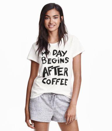 Vit. Ett pyjamasset i mjuk trikå. Kortärmad topp och korta shorts med resår och dragsko i midjan.