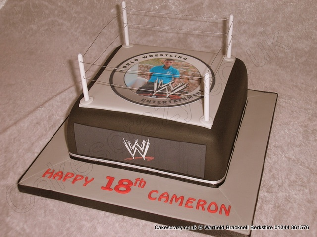 WWE Wrestling Photo Cake. WWE themed celebration birthday cake in the shape of a WWE wrestling ring. Persoanlised with a mock WWE style logo containing an edible photograph