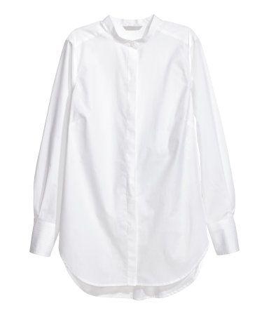 Valkoinen. Pitkähihainen paita puuvillakangasta. Matala pystykaulus ja piilokiinnitys edessä. Leveät kalvosimet, joissa koristesaumat. Pyöristetty helma.