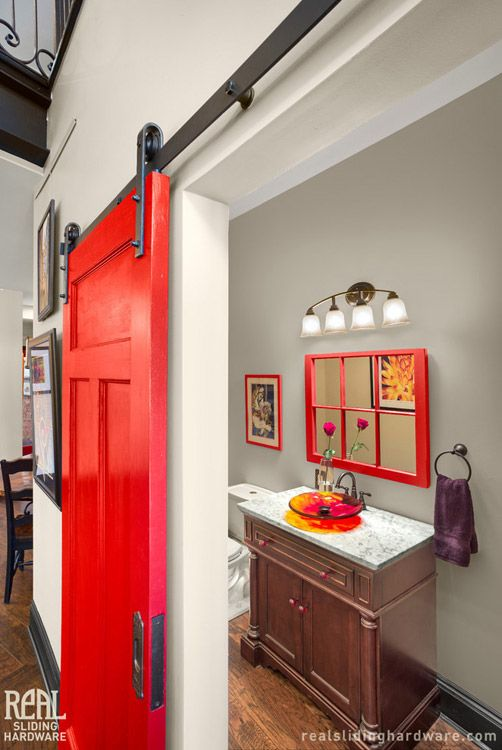 A bright red barn door covers the powder room.