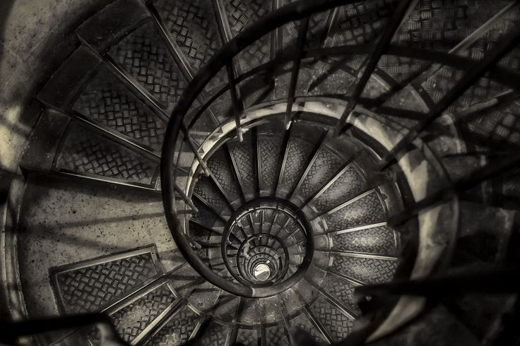 A moody, birdseye view looking down a narrow stairwell at the Arc de Triomphe in Paris, France.