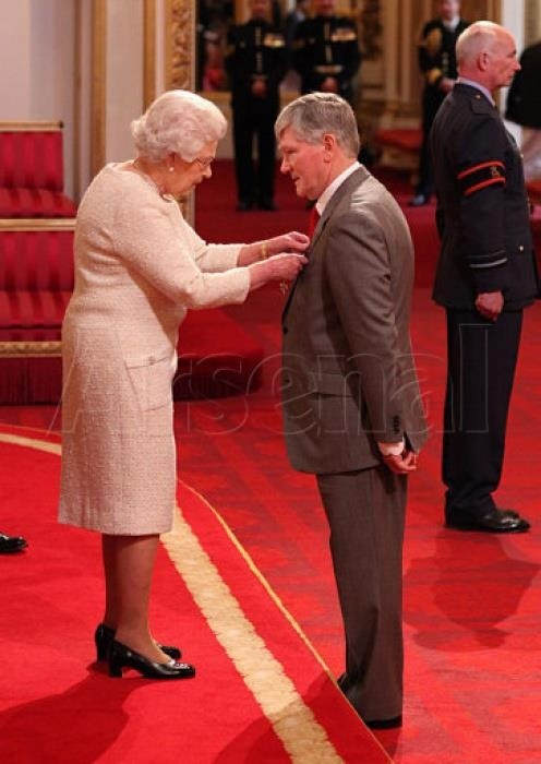 Pat Rice receives MBE from the Queen at Buckingham Palace.