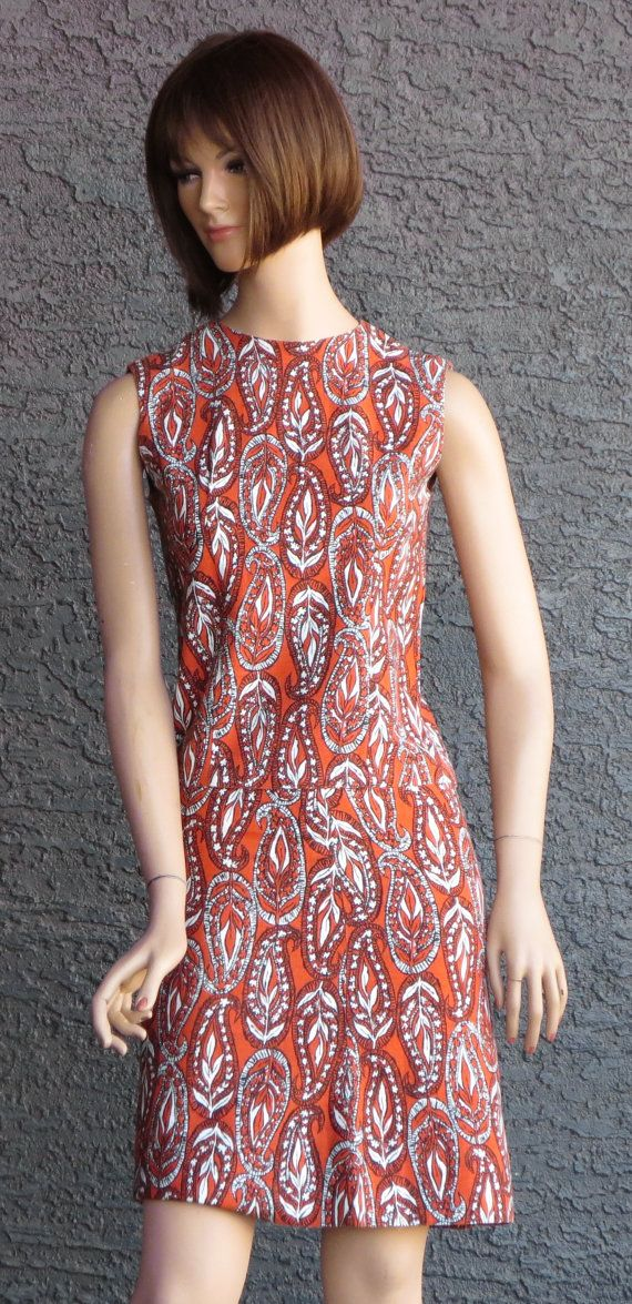 Vintage 1960s 2 piece ladies ensemble with a bell skirt and shell top in a large paisley print represented in burnt orange, black and white with the pattern being designed by Mill Fabrics Corp. This appears to be a handmade item.  The top of this ensemble is a shell that has 5 buttons going up the back. There are slights darts at the armholes with a jewel neckline.  The skirt is a bell shape with a metal zipper and a hook and eye closure to fasten the tab at the waist.   Measurements of Top…
