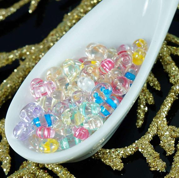 Color: Crystal / Color Lined  Size (mm): 2.5mm x 5mm  Shape: Twin Beads / Czech Twin Beads / Czech Twins / Czech Seed Beads  Sold in packs of 20g.    Twin beads are great addition to Solo beads.  Please note, Pressed Twin beads and Twin beads have slightly different shapes! To compare please search for Pressed Twin beads in our shop.  two hole seed beads, preciosa twin beads, glass twin beads, czech twin beads, twin seed beads, twin beads mix, czech twins, clear two hole b...
