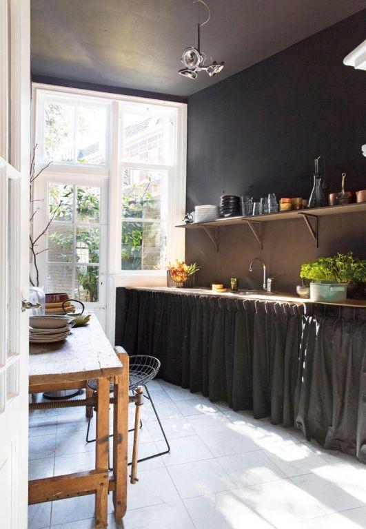 In de keuken zijn muren én plafond geschilderd in kleur Grammafoon van Gamma. Achter het zwarte doek zit de keukenapparatuur verborgen.