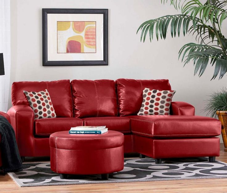 Living room with red leather sectional sofa set and round matching leather coffee table