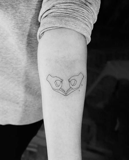 Uterus gang sign tattoo
