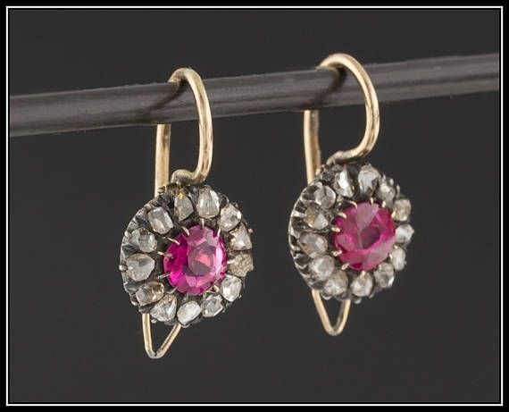 An elegant pair of antique synthetic ruby and diamond earrings from the early 20th century (circa 1900-1910).  These earrings feature synthetic rubies surrounded by a halo of 13 rose cut diamonds set in 14k gold mountings (unmarked, but acid tested). The earrings measure 0.7 inches