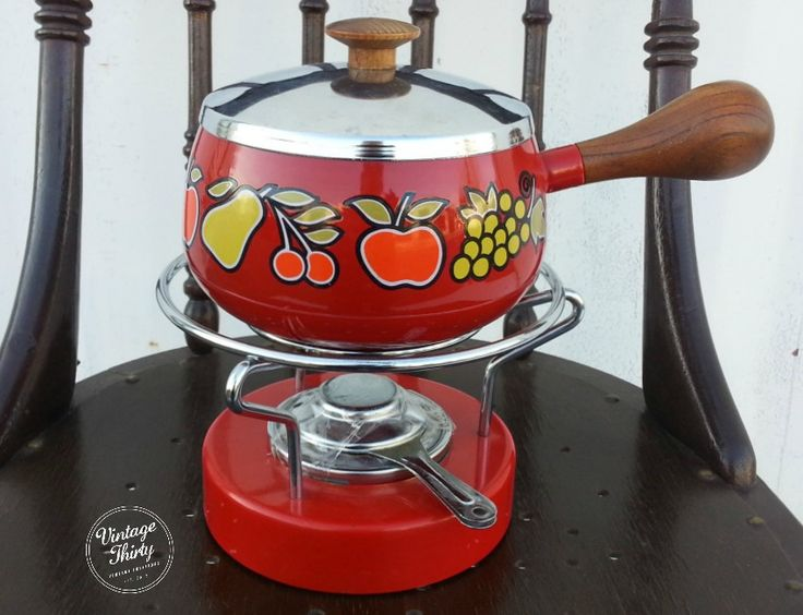 Cherry red Fondue dish with wood handle and fruit motif.