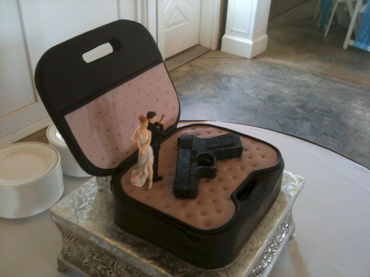 Glock 9mm Pistol Grooms Cake - I made this cake several months ago for a wedding.  The bottom of the gun case is all cake, but the lid is wood coated with fondant.  The gun was molded from a solid piece of modeling chocolate.  The topper was provided by the bride.