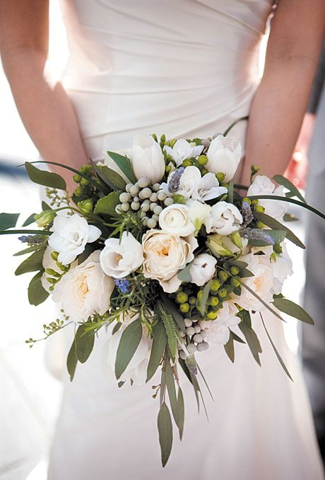 Brides.com: . Bridal Bouquet of Garden Roses, Tulips, Sweet peas, Lavender, and Freesias. This bouquet makes a statement with its large spray of greenery, accented by understated, artfully arranged white blossoms.  See more photos from this Colorado wedding.