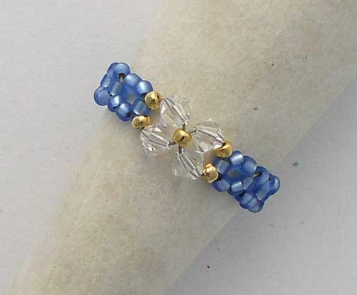 Lisa    Clear Swarovski crystals accented with 22 KT gold seed beads. The band is created from light sapphire satin finish seed beads.