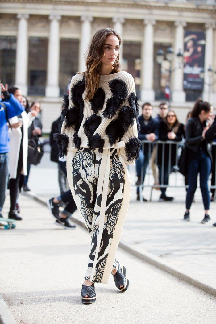 an embellished sweater, printed pants, and platform sandals