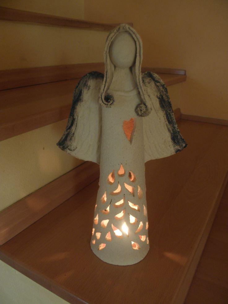 Anděl - svícen Šamotová hlína, nahřívá se a sálá teplo, spodní část ale zůstává chladná. Výška cca 30 cm.